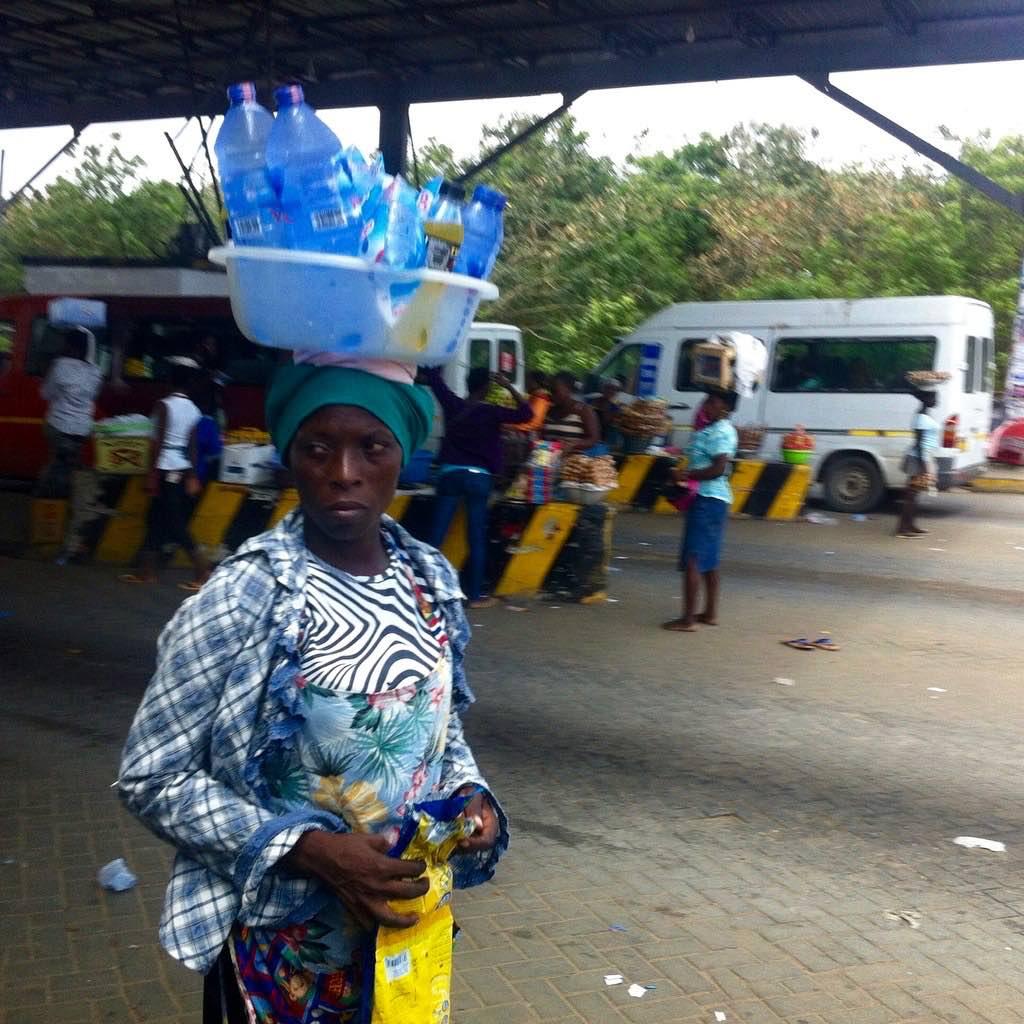 Woman roadside hawking bottled water in Accra, Ghana. #JujuFilms