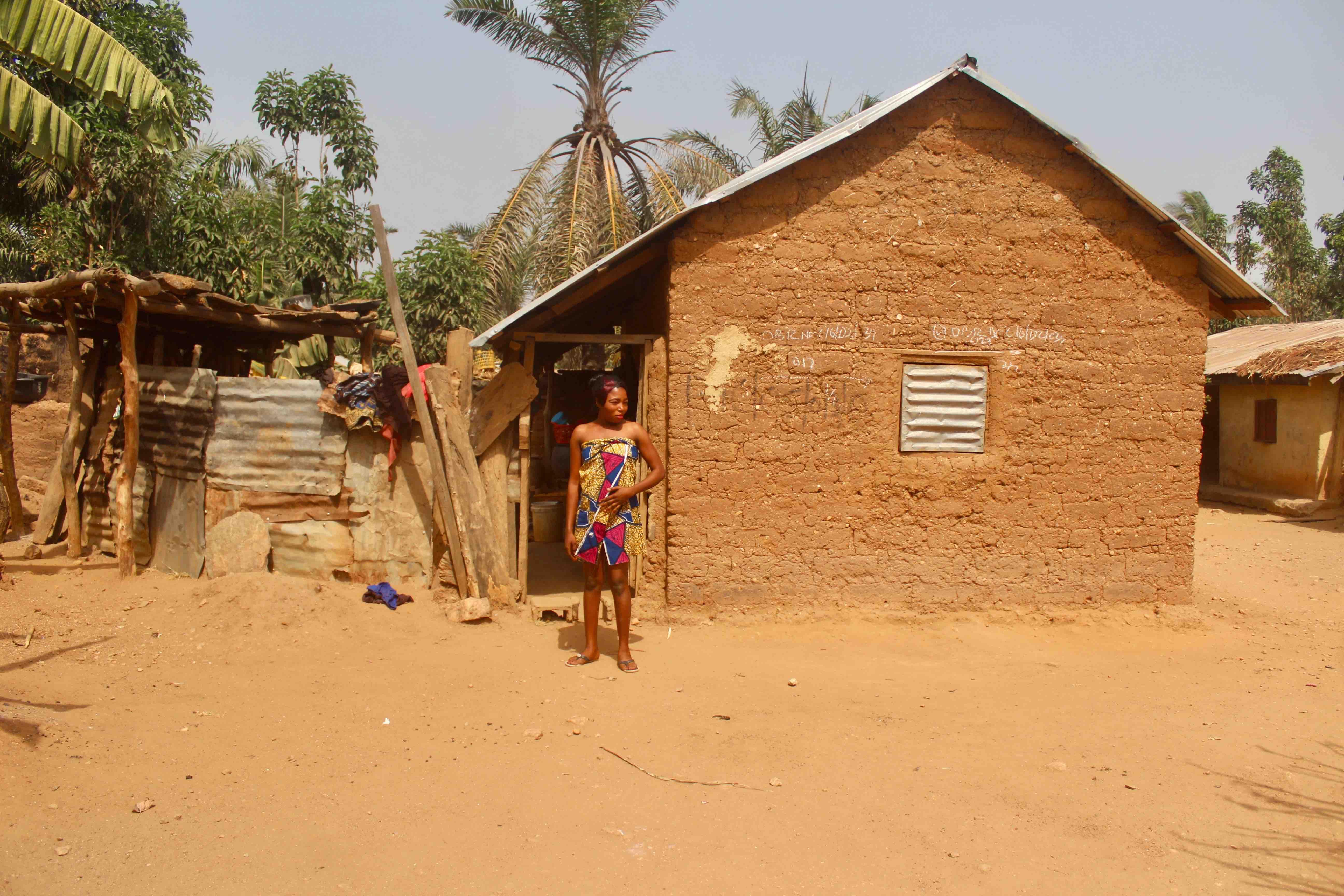 Eggon woman wearing traditional wrapper standing in front of her red mud hut, Langa Langa Village, Nasarawa State, Nigeria. #JujuFilms